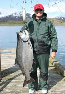Man standing on a dock holding a King Salmon going fishing in Alaska