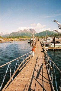 Dock leading down to boats with mountains in the background