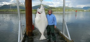 Woman standing on dock with halibut going fishing in Alaska