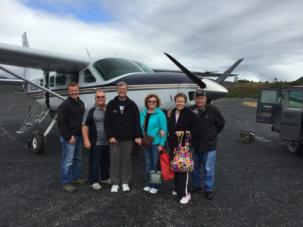 Travel Expert Lisa with Group of men and women standing in front of small aircraft on tarmac