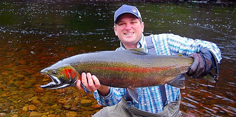 Luxurious Fishing Vacations southeast Alaska steelhead man kneeling